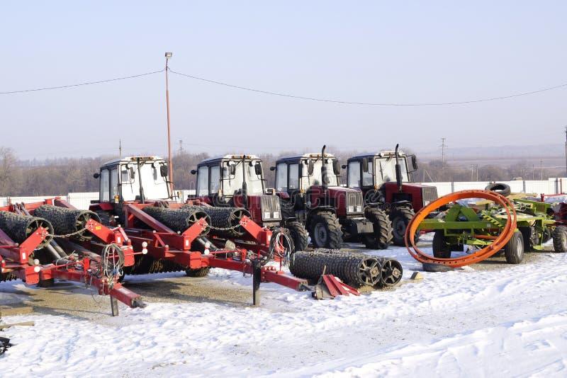 Tratores agrícolas e implementares na loja do inverno imagem de stock