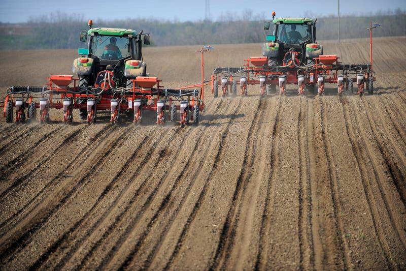 Tratores de exploração agrícola que plantam o campo imagens de stock