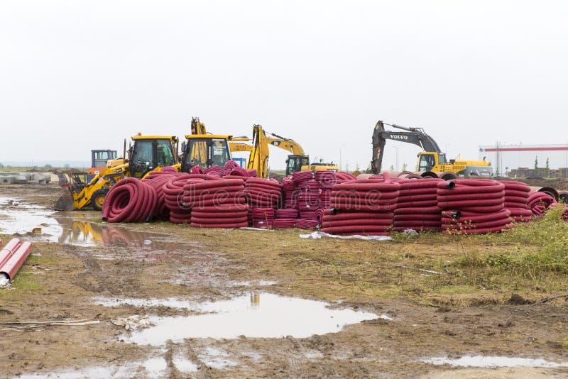 Tratores, escavadoras e tubos do esgoto foto de stock