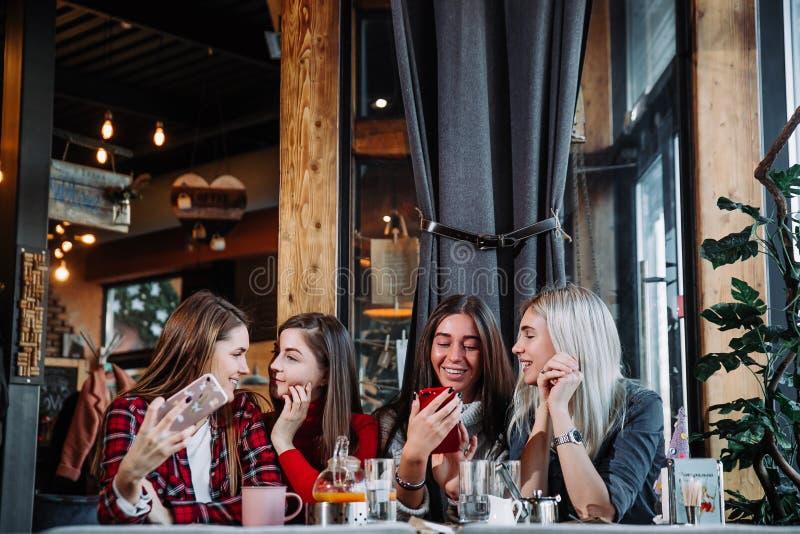 Tratsch durch das Cocktail vier attraktive junge Frauen, die Cocktails im Einkaufszentrum trinken und ein Gespräch mit ihrem habe lizenzfreie stockfotos