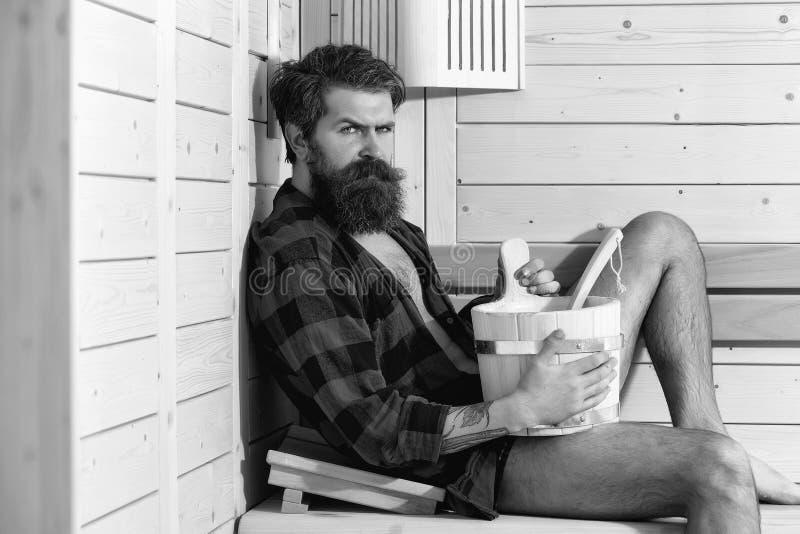 Trattamenti della stazione termale uomo serio barbuto bello nel bagno di legno con il secchio immagine stock libera da diritti