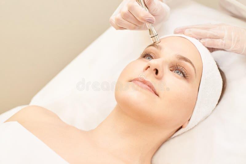 Trattamento del fronte di cosmetologia Ragazza paziente Hardware cosmetico del salone Pelle del diamante di dermatologia pulita immagine stock