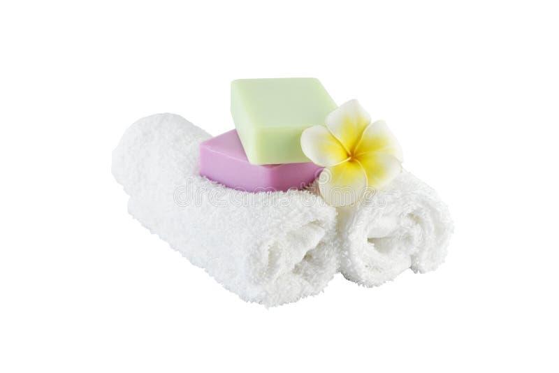 Trattamento della stazione termale con gli asciugamani ed il fiore del sapone su fondo bianco fotografie stock libere da diritti