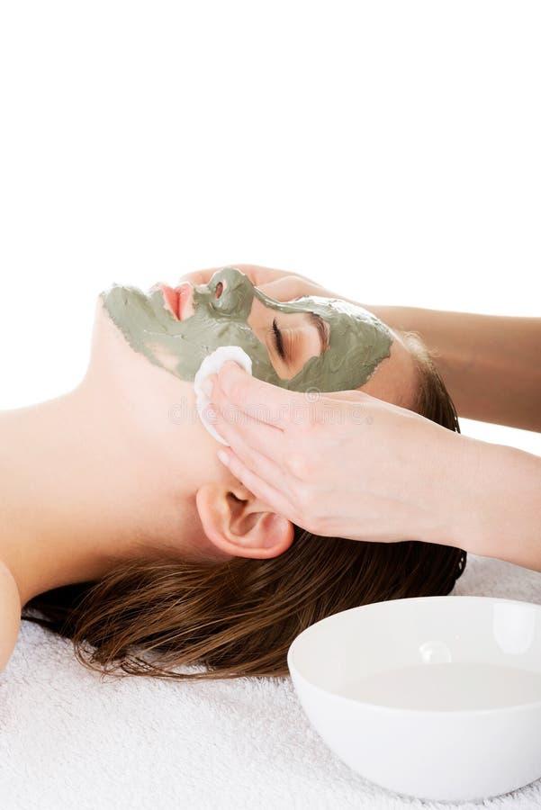 Trattamento di bellezza nel salone della stazione termale. Donna con la maschera facciale dell'argilla. immagini stock
