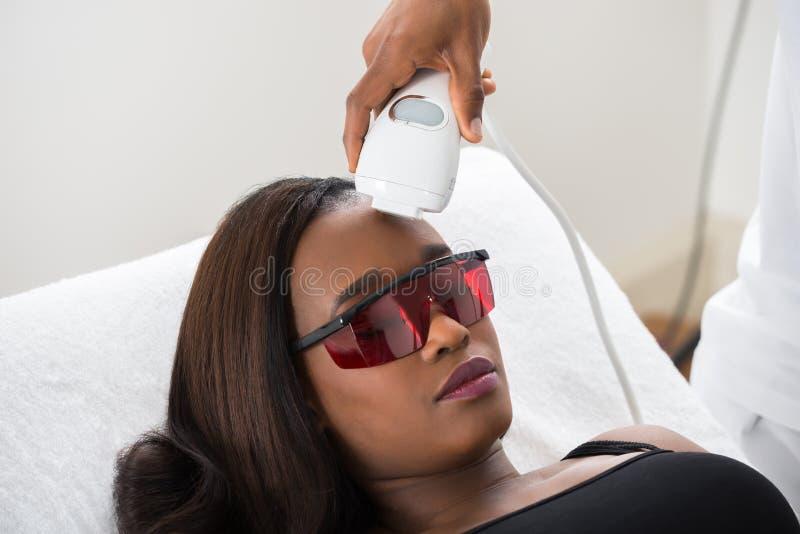 Trattamento di Giving Laser Epilation del terapista alla donna fotografia stock
