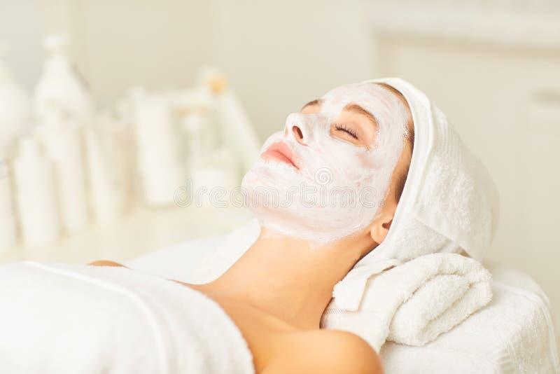 Trattamento facciale della pelle con una maschera cosmetica in un salone di bellezza immagini stock