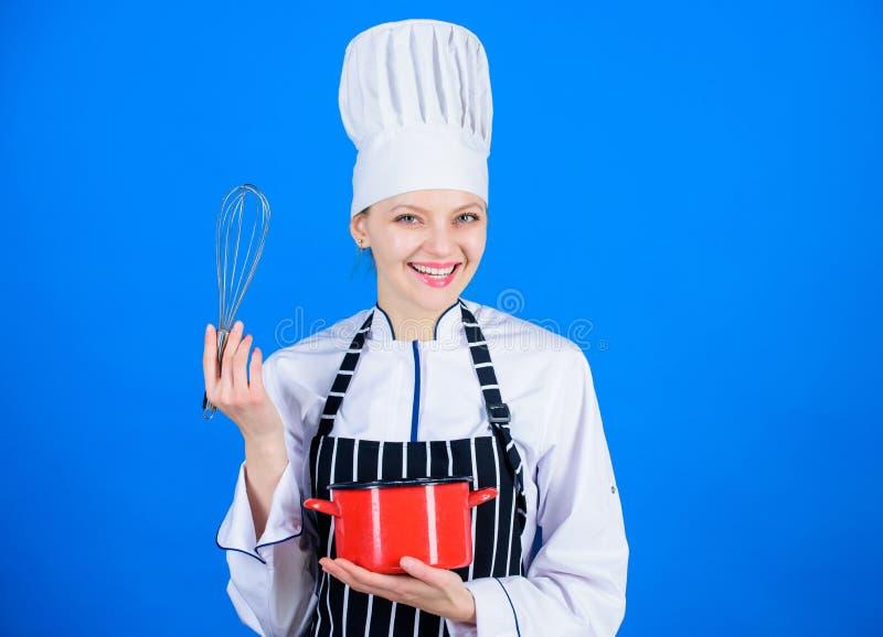 Trattando le mansioni della cucina facilmente Cuoco professionista che sorride con il vaso e che monta strumento in cucina Domest fotografia stock