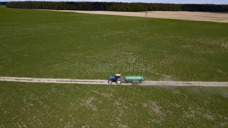 Trattore con il campo di fertilizzazione del rimorchio con concime naturale immagine stock