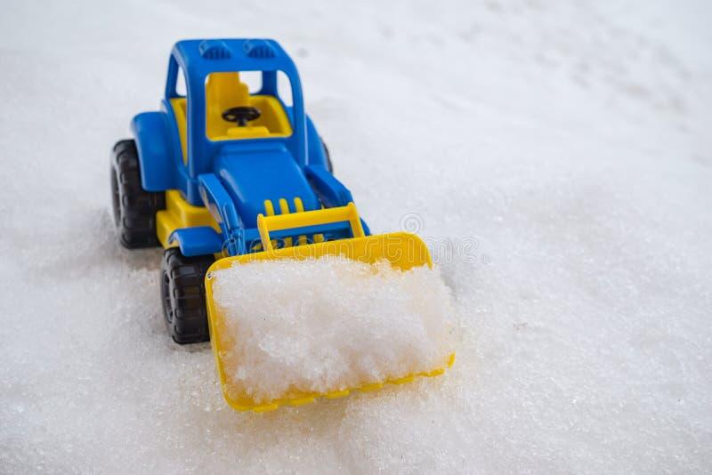 trattore del giocattolo con il caricatore anteriore nella neve concetto delle utilità e della rimozione di neve servizi della str fotografia stock libera da diritti