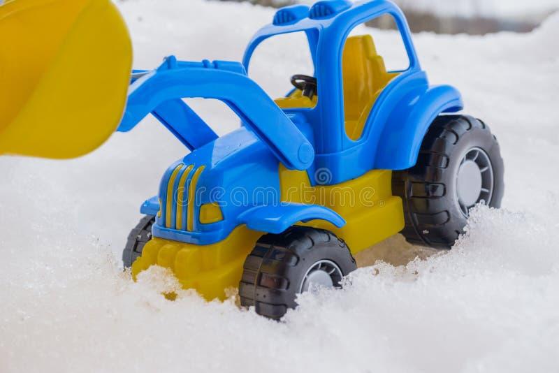 trattore del giocattolo con il caricatore anteriore nella neve concetto delle utilità e della rimozione di neve servizi della str immagini stock libere da diritti