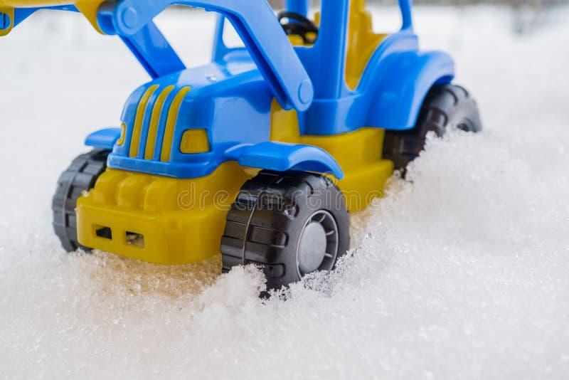 trattore del giocattolo con il caricatore anteriore nella neve concetto delle utilità e della rimozione di neve servizi della str fotografie stock
