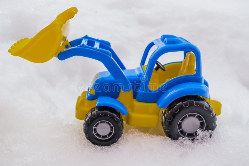 trattore del giocattolo con il caricatore anteriore nella neve concetto delle utilità e della rimozione di neve servizi della str immagine stock