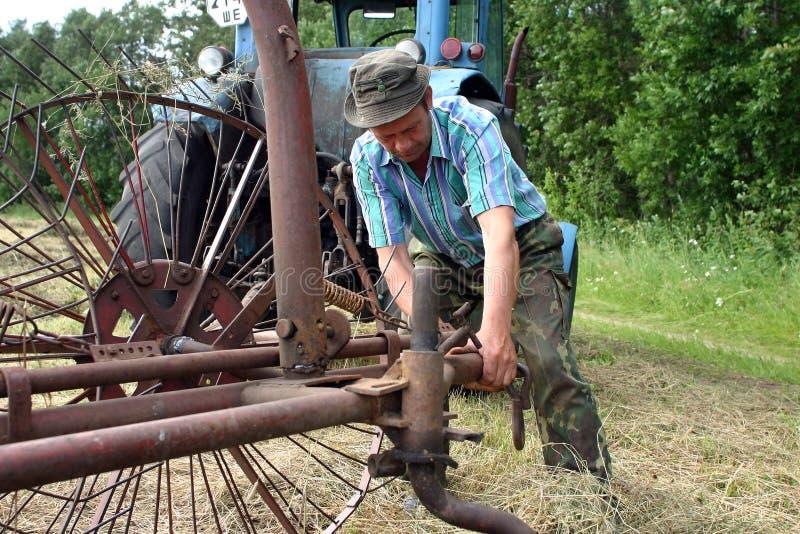 Trattore-driver dell'agricoltore, riparante il vecchio raccattafieno del trattore in falciato in me immagini stock libere da diritti