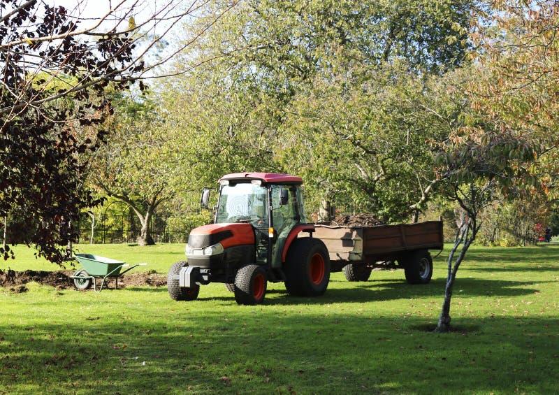 Trattore e carriola per il lavoro nel giardino Trasporto del giardino immagine stock libera da diritti