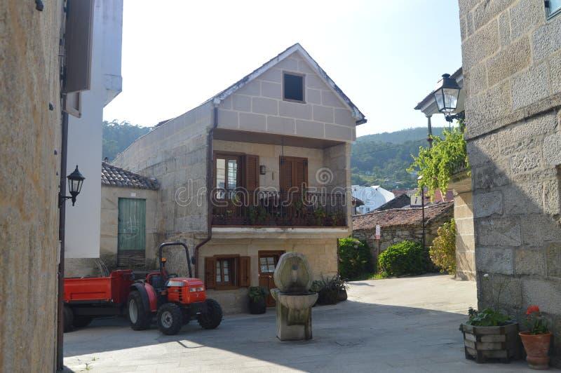 Trattore e fontana di pietra accanto ad una Camera di pietra nel bello villaggio di Combarrro Natura, architettura, storia, via immagini stock libere da diritti