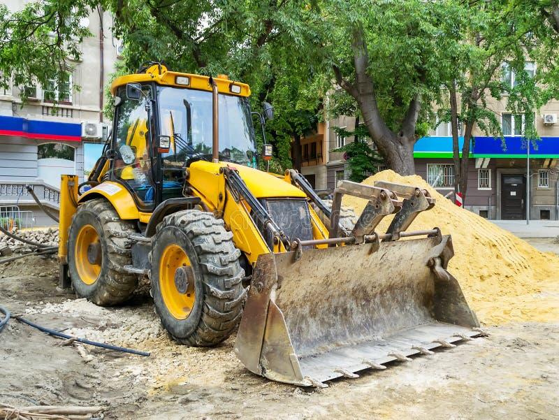 Trattore giallo con un secchio e un grande mucchio della sabbia ad un sito della costruzione di strade su una via della città un  fotografie stock
