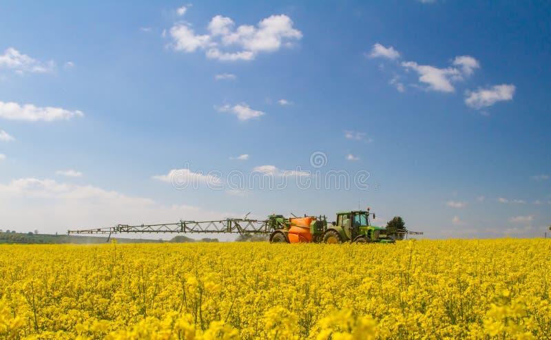Trattore moderno verde che tira uno spruzzatore del raccolto fotografia stock libera da diritti