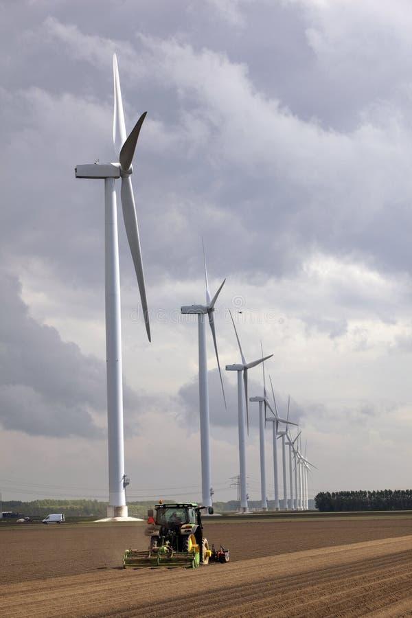 Trattore su terreno coltivabile vicino ai generatori eolici fotografie stock