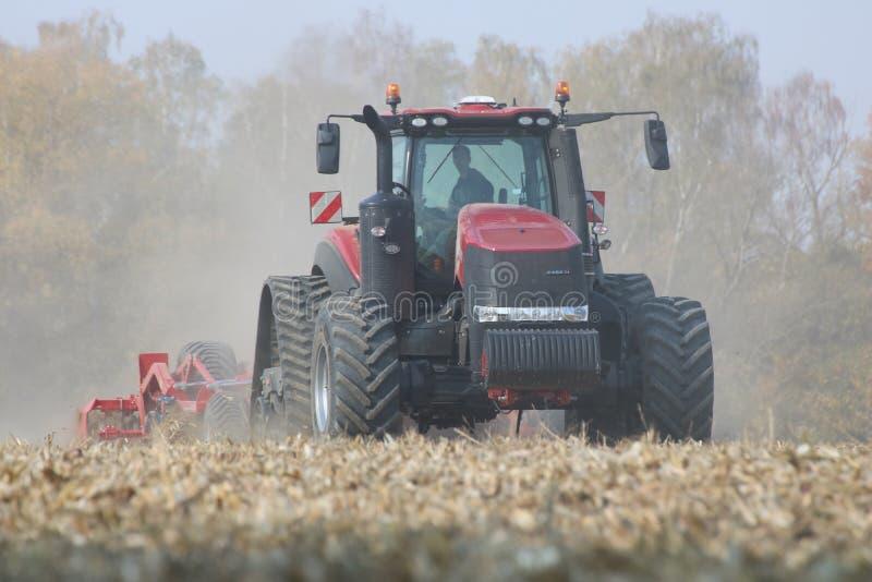 Trattori che lavorano ad un campo di grano in repubblica Ceca fotografia stock libera da diritti
