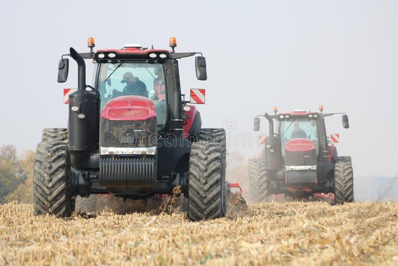 Trattori che lavorano al campo di grano in repubblica Ceca immagine stock libera da diritti