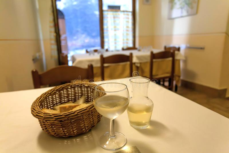 Trattoria italiano tradicional interno Vinho branco na tabela do restaurante velho com pão e das bebidas que esperam visitantes imagem de stock royalty free