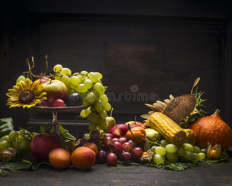 Traube, Äpfel und Herbstobst und gemüse -in einem Eisen rollen mit einer Sonnenblume auf einem Holztisch auf einem dunklen Wandhi stockfoto