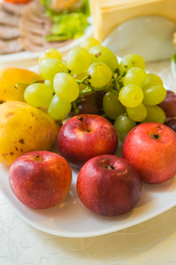 Trauben, Äpfel und Birnen auf einer Platte lizenzfreie stockfotos