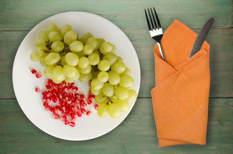 Trauben, Granatapfel auf einem hölzernen Hintergrund Trauben, Granatapfel lizenzfreie stockfotos