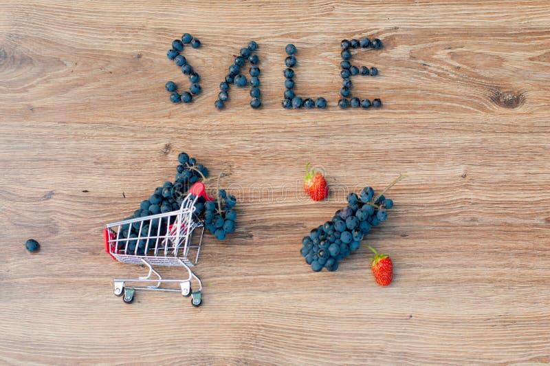 Trauben innerhalb des kleinen Warenkorbes, des Wortverkaufs und des Prozentzeichens stockbilder