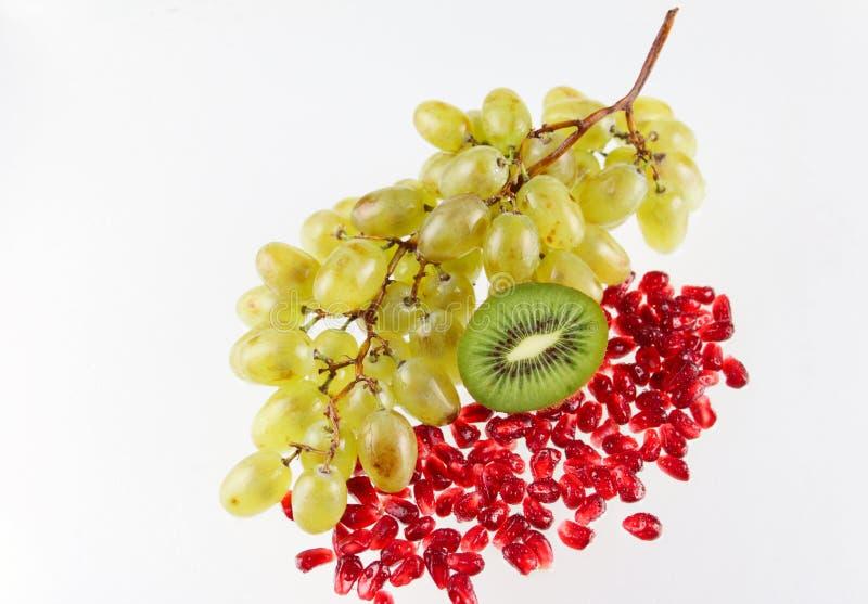 Trauben, Körner eines Granatapfels und Kiwi lizenzfreie stockbilder