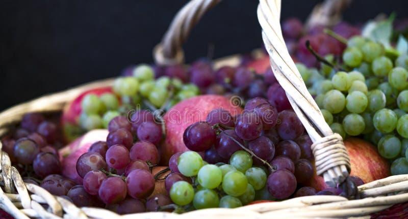 Trauben und Äpfel in einem Weidenkorb lizenzfreies stockfoto
