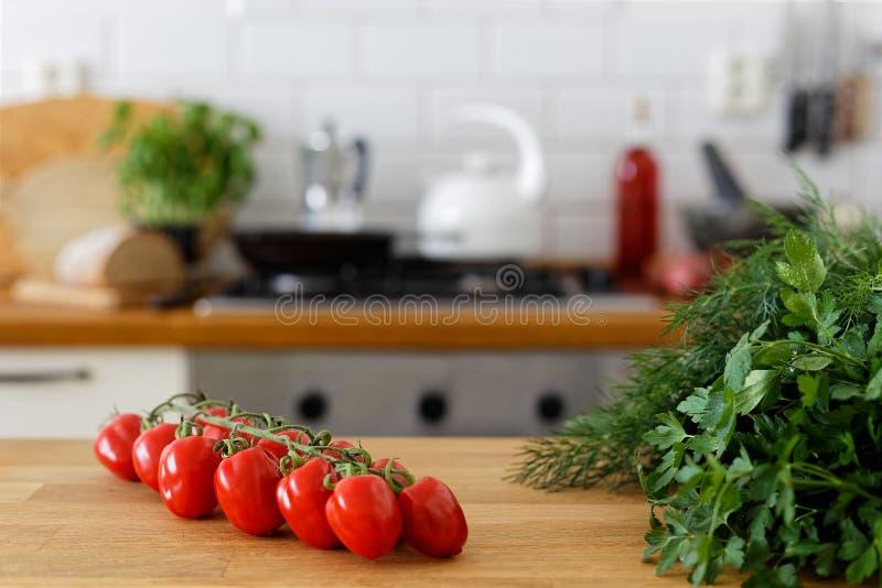 Traubentomaten auf Rebe auf hölzernem Zähler nahe bei frischen Kräutern aus lizenzfreies stockbild