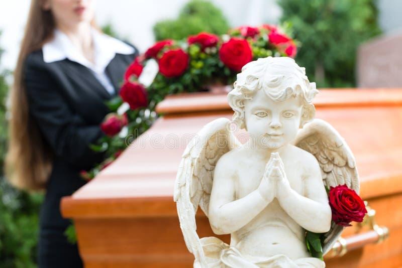 Trauerfrau am Begräbnis mit Sarg stockbild