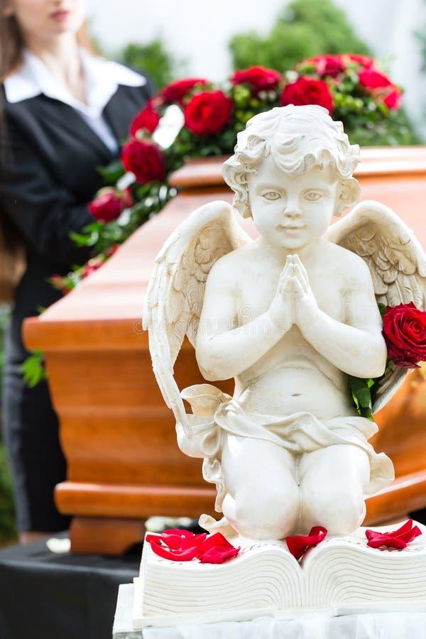 Trauerfrau am Begräbnis mit Sarg stockfotografie
