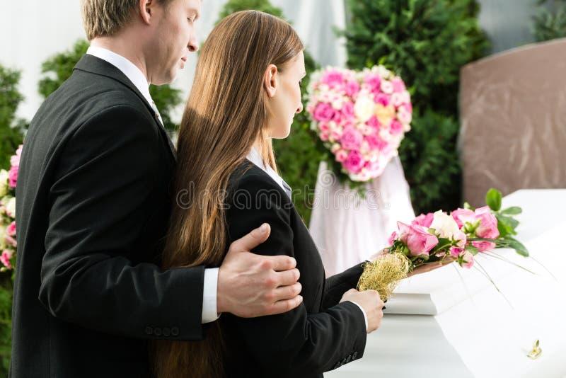 Trauerleute am Begräbnis mit Sarg lizenzfreie stockbilder