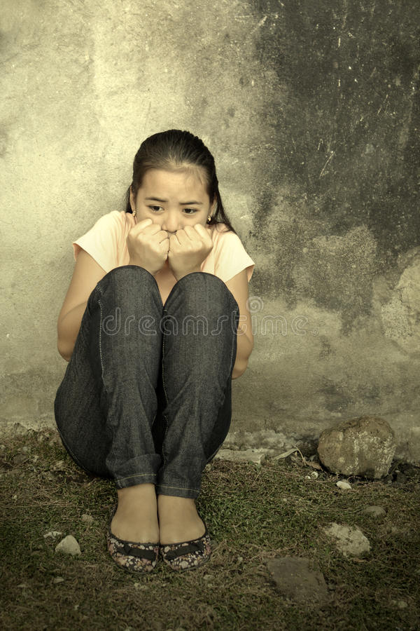 Trauma. Asian teenager with trauma sitting in an abandoned place