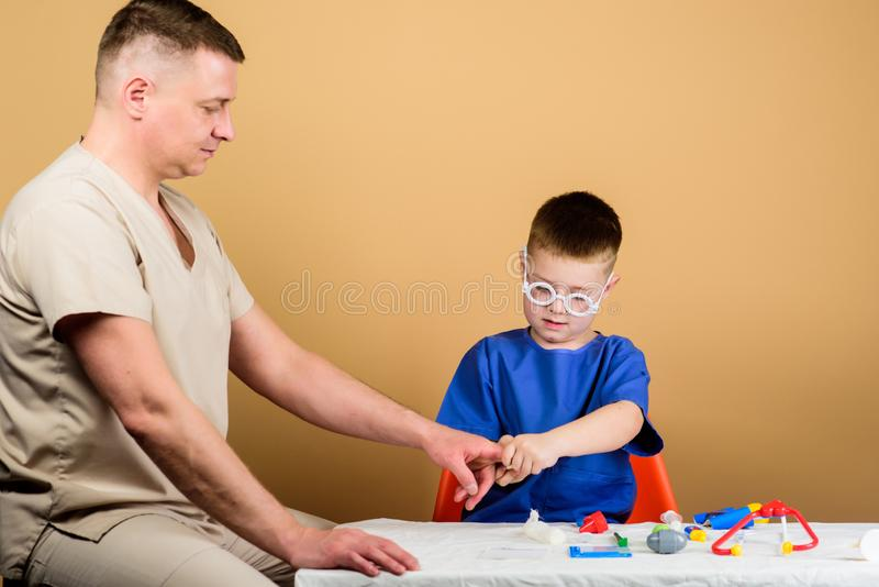 Trauma and injurie. Medicine concept. Kid little doctor sit table medical tools. Health care. Medical examination. Boy. Cute child and his father doctor stock photography