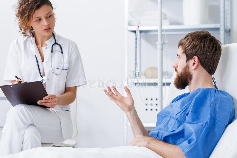Trauma patient talking with nurse. Young patient with trauma talking with recovery nurse stock images