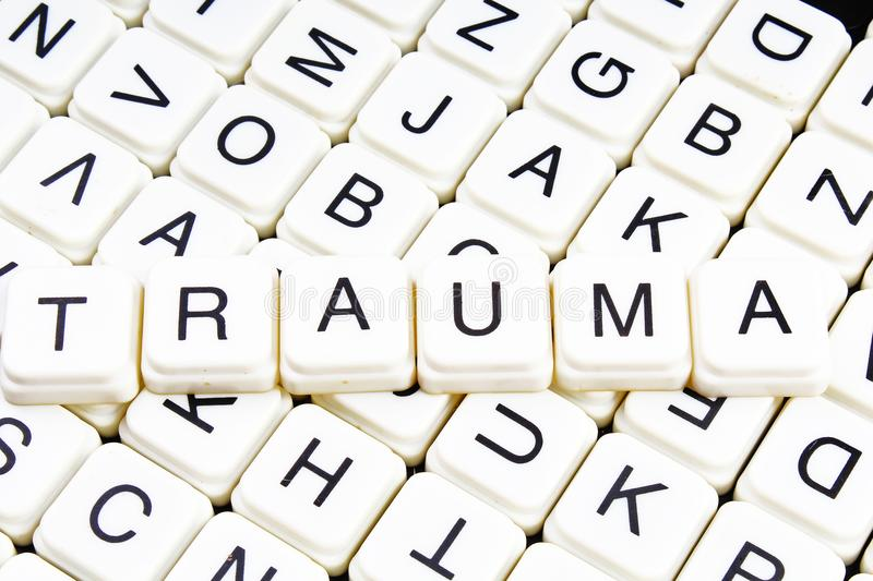 Trauma title text word crossword. Alphabet letter blocks game texture background. White alphabetical letters on black. Background. White educational toy block royalty free stock photo