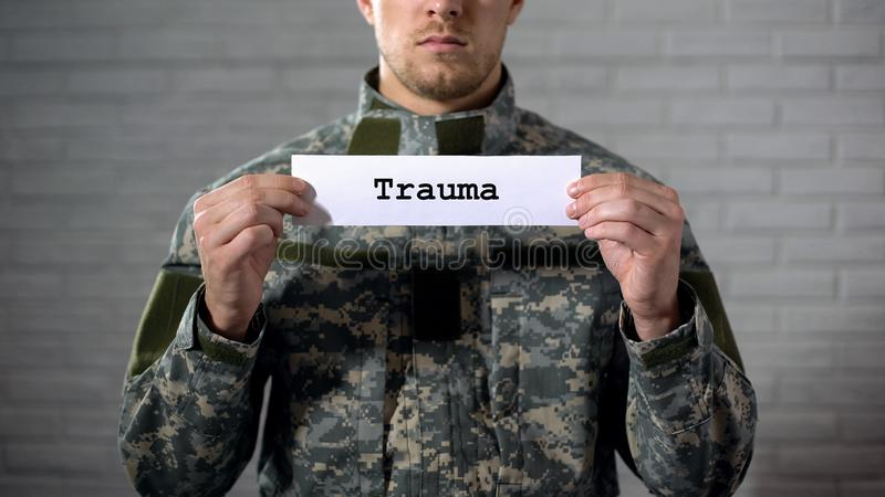 Trauma word written on sign in hands of male soldier, damage to body, health. Stock photo royalty free stock image