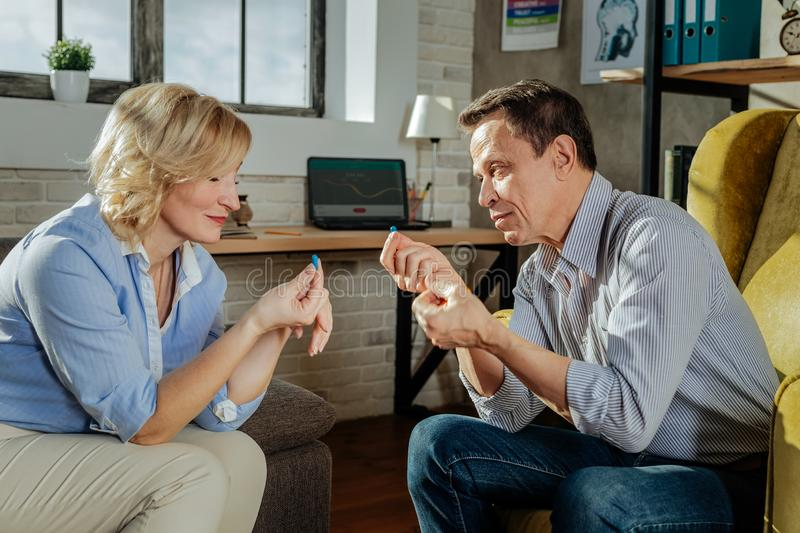 Traumatic couple having middle-age crises and taking pills together. Man proposing. Traumatic couple having middle-age crises and taking pills together while stock photography