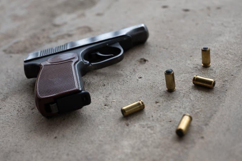 Traumatisch metaalkanon met 9 mm-kogels op een grijze concrete achtergrond het vlakke zijaanzicht, legt, kopieert ruimte stock afbeelding