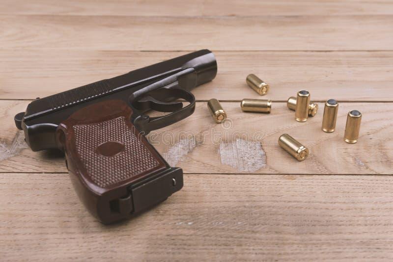 Traumatisch pistool met kogels en patroon op de houten oppervlakte, reeks stock afbeelding