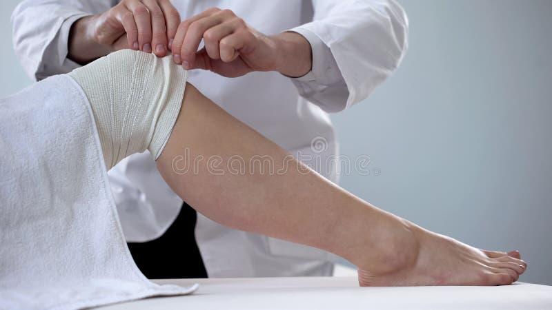 Traumatologist bandażuje pacjentów zwichnął kolano, pierwsza pomoc dla urazów, klinika obrazy royalty free