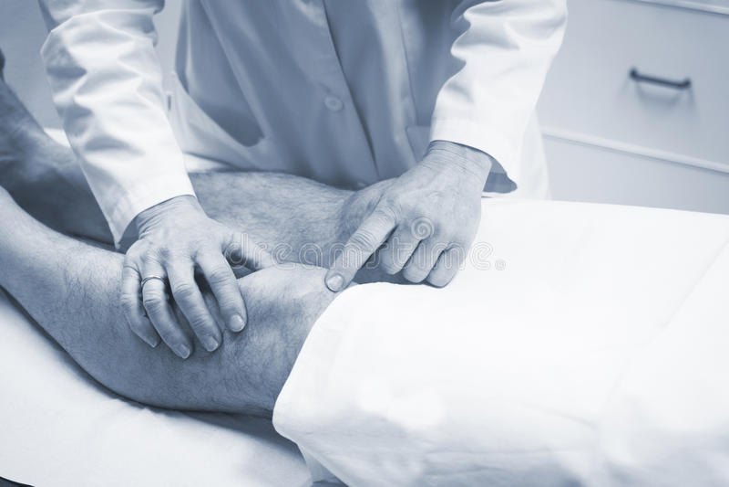 Traumatologist orthopedische chirurg arts die patiënt onderzoeken stock fotografie