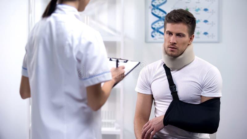Traumatologist que faz prescrições à vítima do acidente, às ataduras no pescoço e ao braço foto de stock