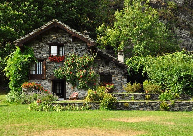 Traumsteinhaus und Garten in den italienischen Alpen stockbilder