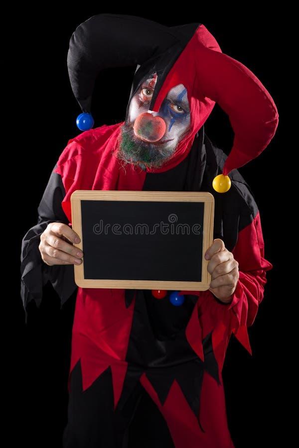 Traurig Clown, der einen Schiefer mit copyspace, schwarzer Hintergrund hält stockfotografie