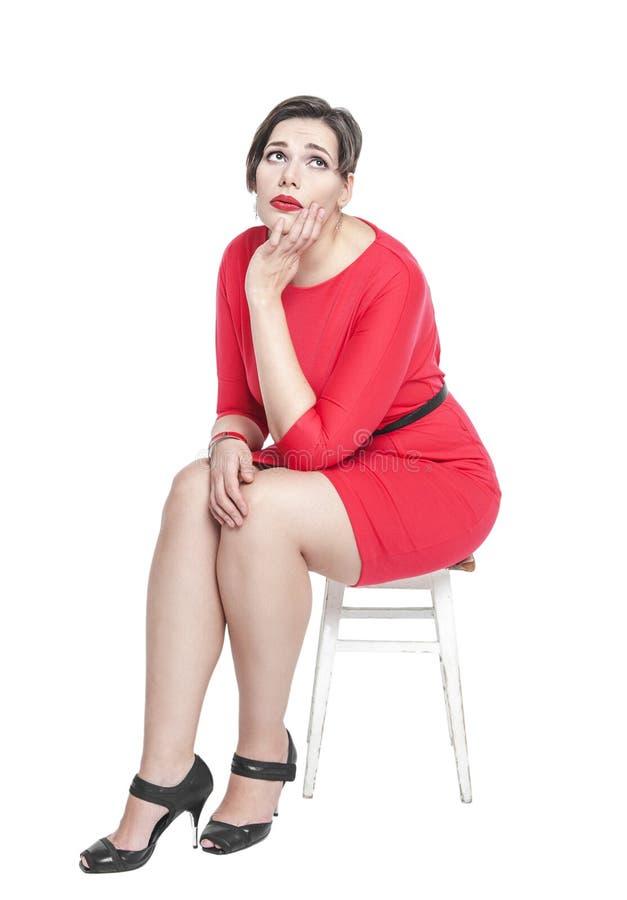 Traurig plus die Größenfrau, die auf dem Stuhl lokalisiert sitzt lizenzfreie stockbilder