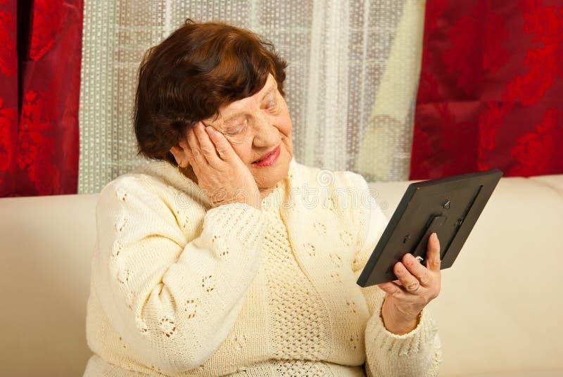 Traurige ältere Frau, die Fotofeld betrachtet stockfotografie